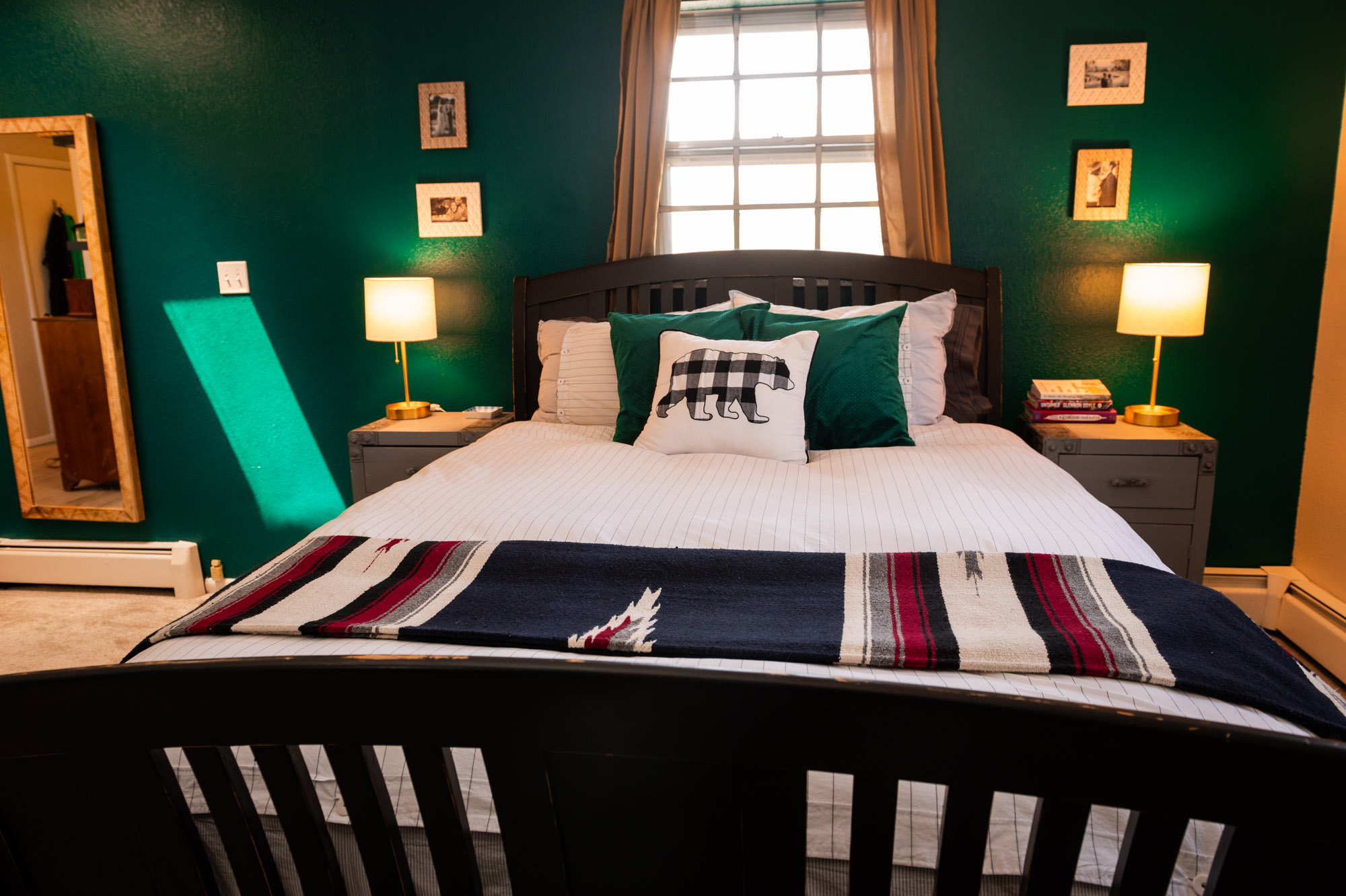 Hovering over the bed with the dark emerald green wall and gold curtains behind it