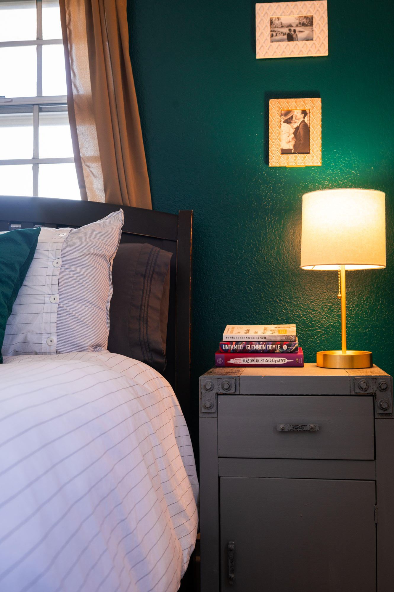 Detail shot of our bedside tables with gold lamps and pictures