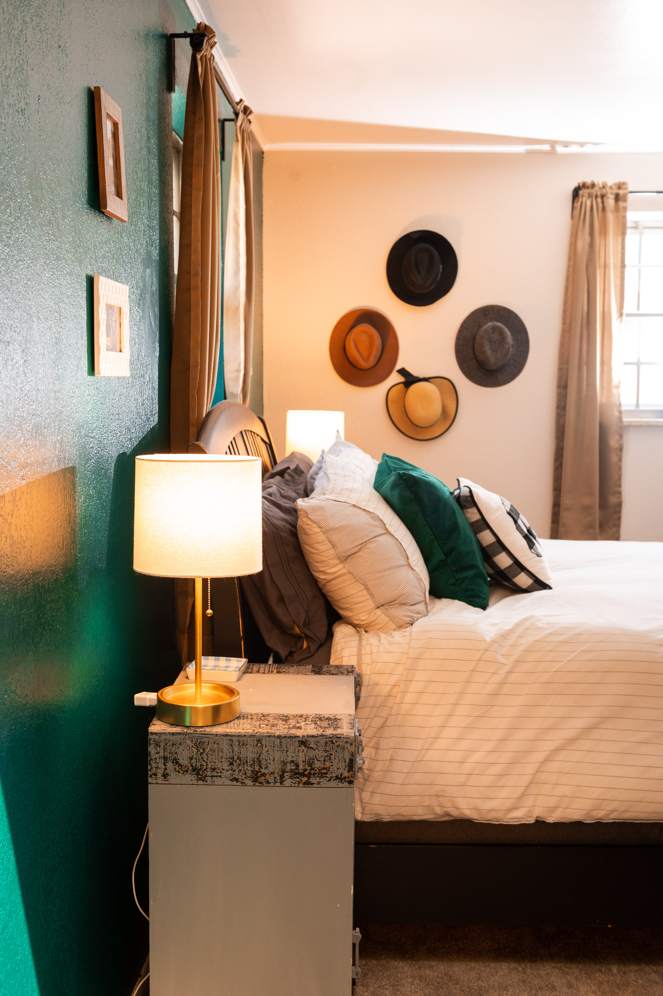 Side view of our west elm bedspread agains the emerald green wall