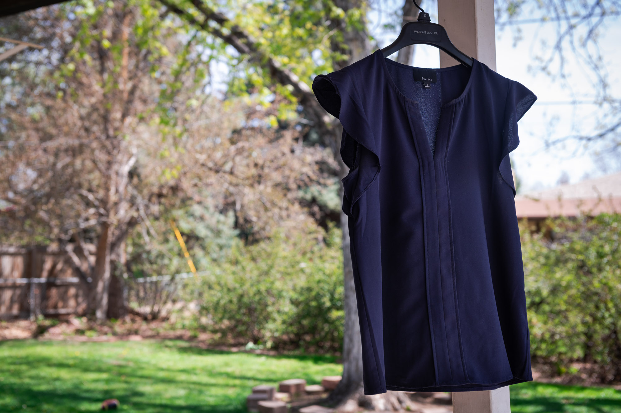Blue flowy blouse blowing in the breeze while hung outside