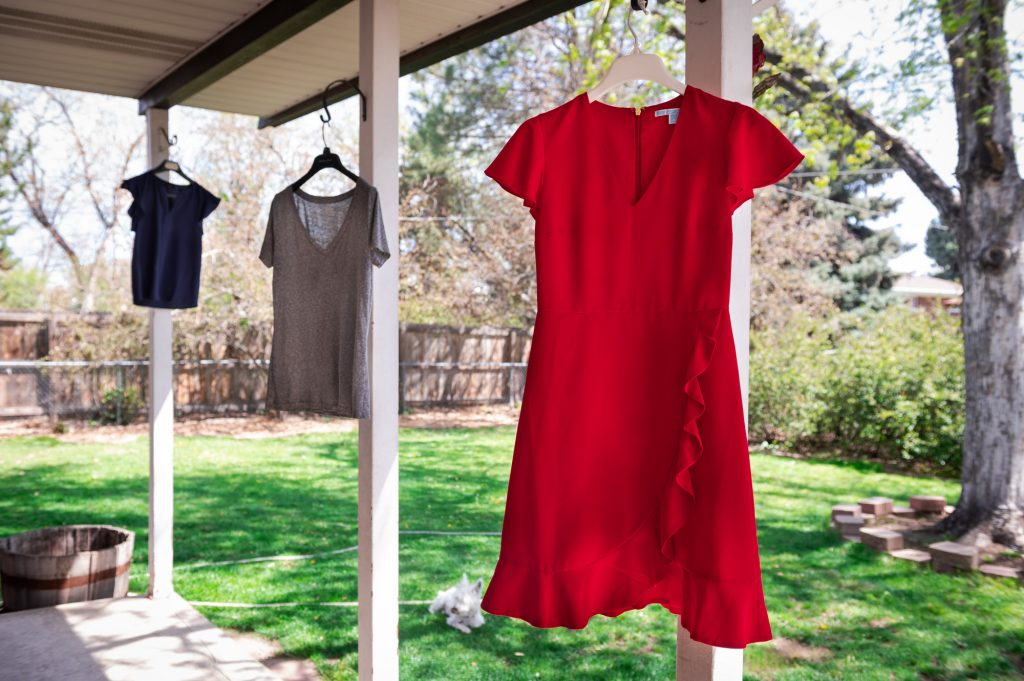 Summer basics hanging outside on the porch. Red Dress, T-shirt, flowy blouse